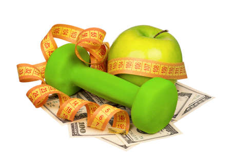 Dumbbells with apple and measure tape on heap of dollars isolated on a white background photo