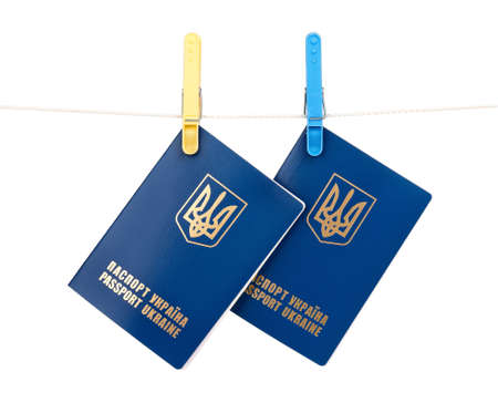 Clothes-pegs holding two international Ukrainian passports on a rope isolated on white background Stock Photo - 15540983