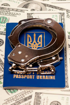 International Ukrainian passport with handcuffs on US dollars background Stock Photo - 15556705