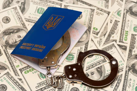 International Ukrainian passport with handcuffs on US dollars background Stock Photo - 15597811