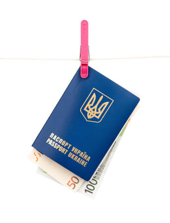Clothes-peg holding international Ukrainian passport with Euro banknotes on a rope isolated on white background Stock Photo - 15597626