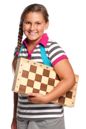 Schoolgirl with chessboard - isolated on white background photo