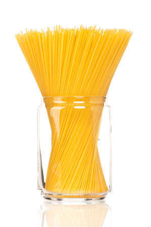 Spaghetti in glass pot isolated on white background photo