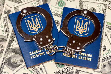 Two international Ukrainian passport with handcuffs on US dollars background Stock Photo - 15678246