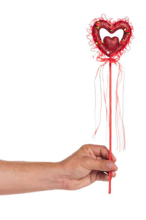 Man hand with heart on a stick with red ribbon isolated on white background photo