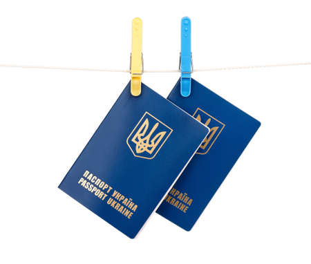 Clothes-pegs holding two international Ukrainian passports on a rope isolated on white background photo