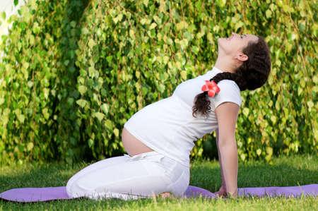 mujeres embarazadas: Feliz mujer embarazada se relaja en el parque al aire libre