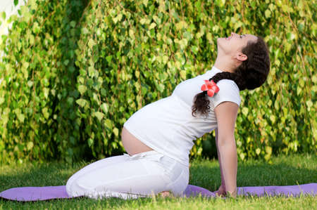 pregnant woman yoga: Happy pregnant woman relaxing in the park outdoors