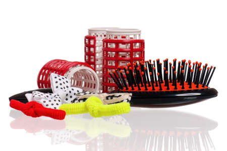Red hair curlers and hairbrush isolated on white background photo