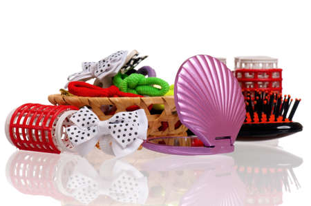 Set of cosmetics - hairbrush, hair curlers and small mirror isolated on white background photo