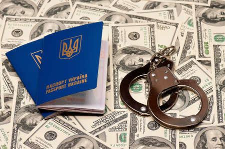 Two international Ukrainian passport with handcuffs on US dollars background Stock Photo - 15935695