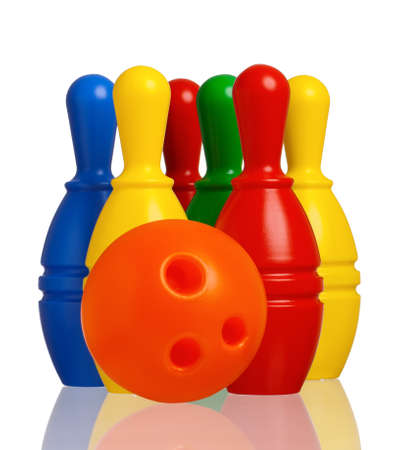 Colorful plastic skittles of toy bowling with orange ball isolated on a white background photo