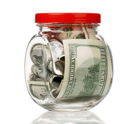 meanness: Many dollars in a glass jar isolated on white background Stock Photo