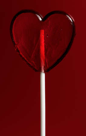 Single heart-shaped lollipop of valentines day on red background Stock Photo - 16384451