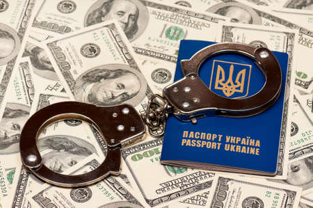 International Ukrainian passport with handcuffs on US dollars background Stock Photo - 16384998