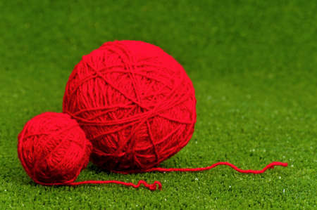 weave ball: Red ball of yarn on green artificial grass Stock Photo