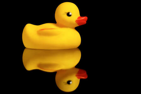 Cute yellow rubber duck on black background photo