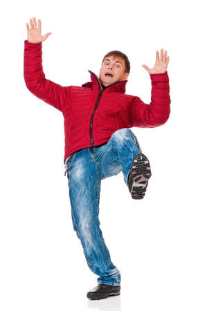 slip: Full length portrait of a young man dressed with winter clothes slipping on floor isolated on white background