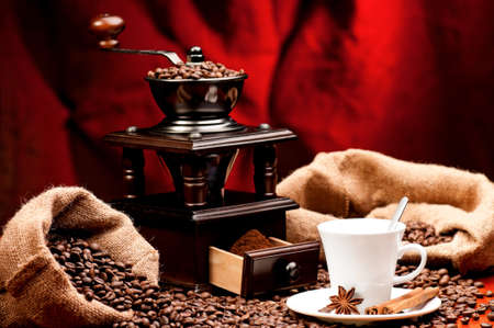 Coffee grinder and cup of coffee with spices on dark red background photo