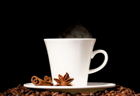 Coffee cup with spices on black background photo