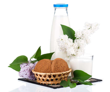 Bottle of milk with cookies and branch of lilac isolated on white background photo