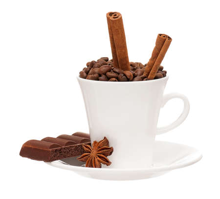 White cup with coffee beans, spices and chocolate isolated on white background photo