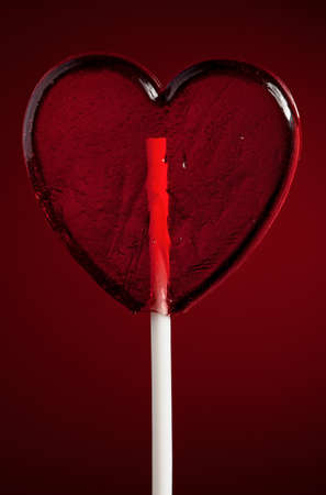 Single heart-shaped lollipop of valentines day on red background photo