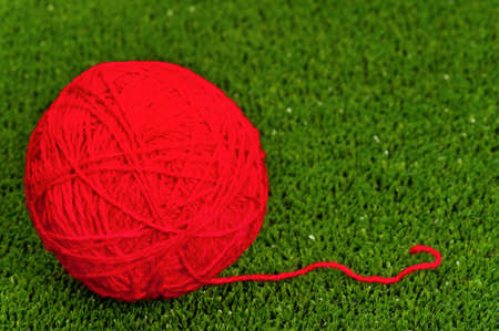 Red ball of yarn on green artificial grass photo