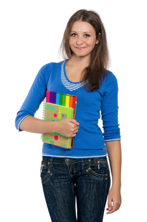 Beautiful teen girl with exercise books posing on white background photo