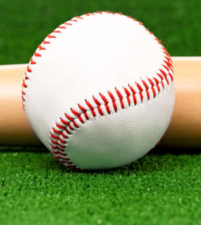 Close-up of baseball ball and bat on artificial green grass photo