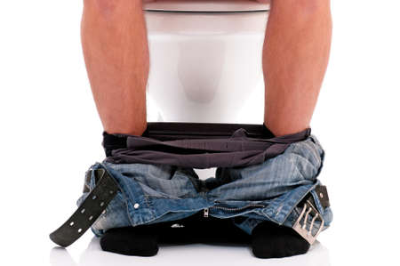 Man is sitting on the toilet bowl, on white background Foto de archivo