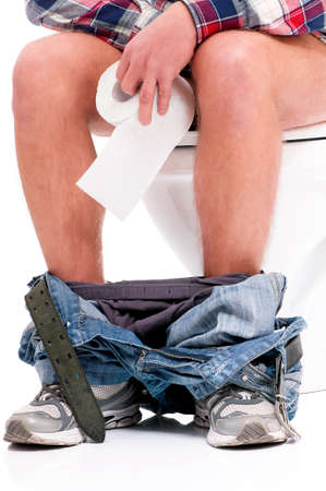 poo: Man is sitting on the toilet bowl, holding paper in hands, on white background