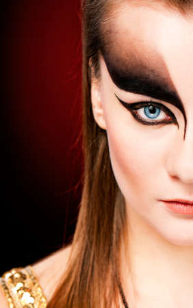 Close-up shot of beautiful young woman face with stylish black make-up photo
