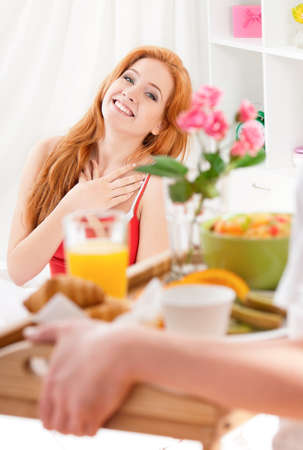 Man serving breakfast for his wife in bed at home photo
