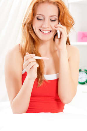 Beautiful young woman talking on cell phone and smiling at pregnancy test Stock Photo - 18940437