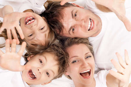 Portrait of a cheerful family having fun together lying on a bed at home - top view photo
