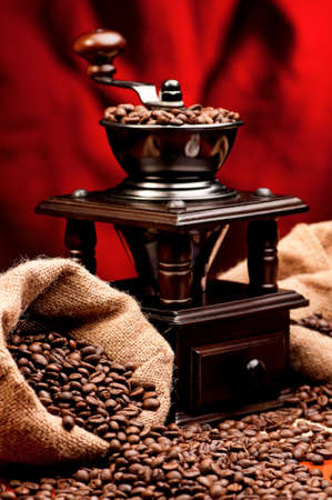 Coffee grinder and beans coffee on dark red background photo