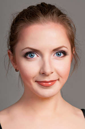 Portrait of beautiful young woman with make-up on gray background photo