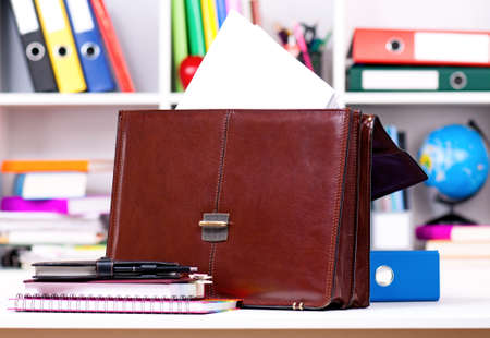 Brown leather briefcase on table at office photo