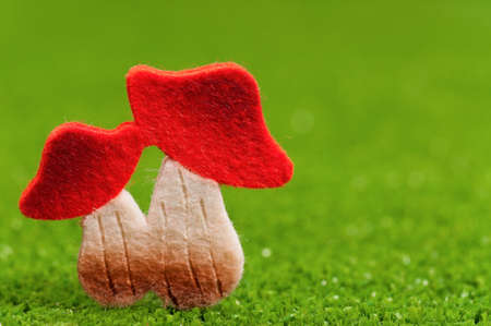 Artificial small mushrooms on artificial green grass photo