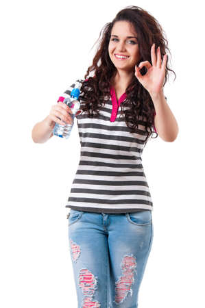 Happy beautiful girl with bottle of water showing ok sign, isolated on white background photo