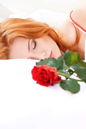 Beautiful girl is sleeping on white bed  Flower on a pillow next to her  photo