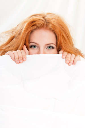 Closeup portrait of a beautiful young woman with red hair and green eyes under the blanket photo
