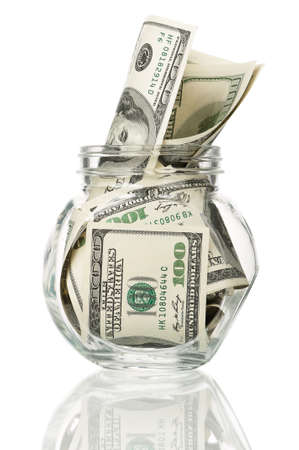 Many dollars in a glass jar isolated on white background photo