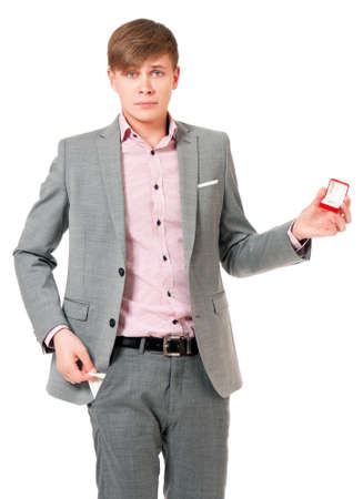 Unhappy young man in suit holding box with wedding ring, isolated on white background photo