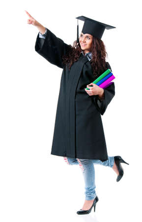 Young graduate girl student in mantle with books showing something, isolated on white background photo
