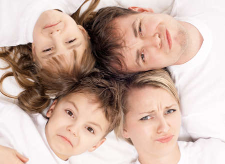 displeased: Portrait of a  displeased family having fun together lying on a bed at home - top view