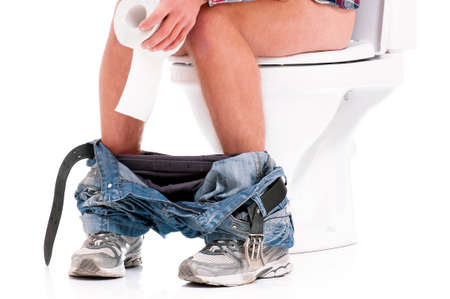 urine: Man is sitting on the toilet bowl, holding paper in hands, on white background
