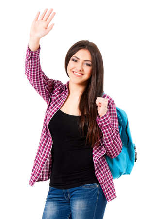 Smiling student girl with backpack greets with her hand, isolated on white background photo