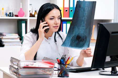 Female doctor looking at x-ray and talking by phone